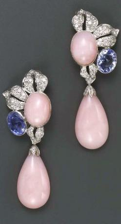 A pair of pink opal, sapphire, diamond and fourteen karat white gold pendant earrings each designed as a pavé-set diamond foliate cluster centering an oval cabochon pink opal and accented by an oval-shaped light blue sapphire, suspending a detachable pink