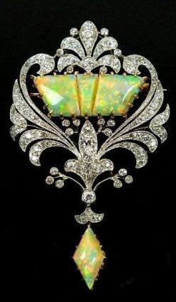An early 20th century diamond and opal set brooch, designed as a three panel opal centre within old cut diamond set openwork scroll border, all supporting opal drop, all claw, collet and pave set in yellow and white metal, the reverse with detachable broo