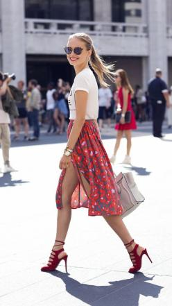Shop this look on Lookastic: http://lookastic.com/women/looks/sunglasses-crew-neck-t-shirt-bracelet-watch-midi-skirt-tote-bag-heeled-sandals/8279 — Navy Sunglasses — White and Black Print Crew-neck T-shirt — Gold Bracelet — Gold Watch — Red Print Midi Ski