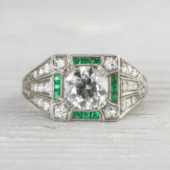 1.01 Carat Art Deco Vintage Emerald & Diamond Engagement Ring.  Center diamond is prong set inside a square setting. Accented with single cut diamonds and calibre cut emeralds. Decorated with MILLEGRAIN edges and elaborately hand engraved. Beautiful d