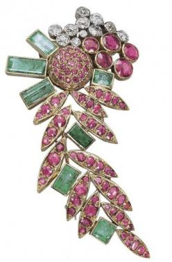 A RUBY, EMERALD AND DIAMOND CLIP BROOCH, BY SUZANNE BELPERRON Designed as a stylized floral spray, the ruby leaves interspersed with rectangular-cut emerald collets to the circular-cut ruby and diamond collet-set surmount, circa 1950, 7.6 cm, with French