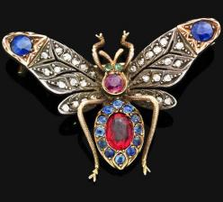 An antique gem-set butterfly brooch Modelled as a butterfly, the pierced outstretched wings set with single-cut diamonds and circular-cut sapphires, the body designed as a ruby and sapphire cluster, to the emerald eye and ruby head detail, mounted in silv
