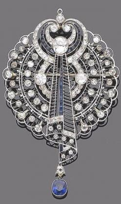 An early 20th century sapphire and diamond brooch pendant The openwork plaque of fine knife-wire, millegrain set brilliant and single-cut diamond detail, its centre issuing a stylised scroll of similarly set diamonds and calibré-cut sapphires, to an oval