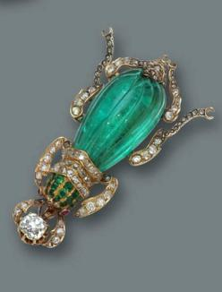 An emerald, diamond and ruby brooch in the form of a beetle, with a fluted emerald body, old European and rose-cut diamond legs, calibré-cut emerald head and cabochon ruby eyes; estimated total diamond weight: 2.00 carats; mounted in eighteen karat gold