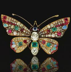 GEM-SET AND DIAMOND BROOCH, CIRCA 1900 Designed as a butterfly, the head and thorax respectively set with a step-cut sapphire and an emerald and oval and pear-shaped diamonds, the wings set with variously shaped rubies, opals, emeralds and diamonds.