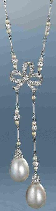 A natural pearl and diamond lavallière, circa 1910.  The fine chain composed of old brilliant-cut diamond and seed pearl trios, connected by platinum baton links, suspending a central old brilliant-cut diamond bow motif, terminating in two natural pearl d