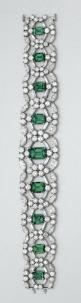 EMERALD AND DIAMOND BRACELET, CARTIER The highly flexible openwork band set with 9 emerald-cut emeralds weighing approximately 14.00 carats, within stylized circular frames set with 108 round, 36 baguette and 36 marquise-shaped diamonds, altogether weighi