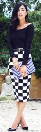 Checkerboard pencil skirt with a beautiful blouse to match the entire outfit, blue shoes, and a grey clutch-style pocketbook.